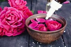 Puchar z czerwieni róży płatkami na tle ciemne drewniane deski i istotny olej z różami zdjęcia royalty free