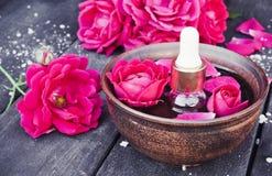 Puchar z czerwieni róży płatkami na tle ciemne drewniane deski i istotny olej z różami fotografia royalty free