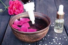 Puchar z czerwieni róży płatkami na tle ciemne drewniane deski i istotny olej z różami obraz stock