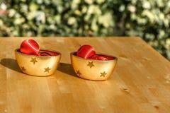Puchary i Bożenarodzeniowe piłki na drewnianym stole Obrazy Stock