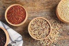 Puchary z różnymi typami quinoa na drewnianym tle obraz stock