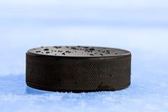 Puck on blue ice. Black hockey puck on blue ice Stock Photos