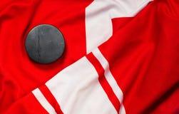Puck på en röd hockeyärmlös tröja arkivfoton