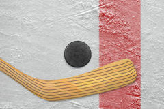 Puck and stick on the red line Royalty Free Stock Photos