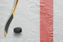 Puck and stick on the Red Line. The puck, stick at the red line on a hockey rink. Texture, background stock photography