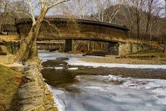 Puckelrygg täckt bro över en djupfryst ström Arkivbilder