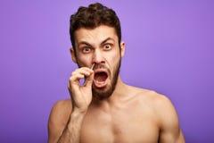Pucking näshår för emotionell rolig man med pincett royaltyfria bilder