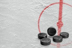 Pucks en een fragment van de hockeyarena met een centrale cirkel stock foto
