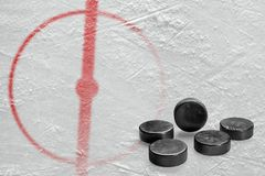 Pucks and a fragment of the hockey arena with a central circle. Fragment of the hockey arena with markings and washers. Concept, hockey royalty free stock image