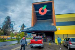 PUCON, CHILE - SEPTEMBER, 23, 2018: Tourists walking close to gorgeous wooden colonial buildings and some cars parked in. The parking area, located in the city stock photo