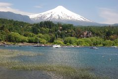 Pucon, snowy volcano Villarrica from Villarrica Lake, Chile. Pucon, overlooking the snowy volcano Villarrica from from Villarrica Lake with harbour and houses Stock Photos