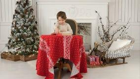 Puctures les explorant de sourire de garçon dans le livre se reposant à la table près de l'arbre de Noël Photos stock