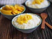 Pudín de arroz con el atasco del mango en cuencos con las cucharas de madera Imagen de archivo libre de regalías