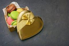 Pudín francés de la pasta de azúcar del chocolate Macarrones o macarons multicolores dulces en caja de regalo de oro hermosa Imagenes de archivo