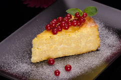 Pudding cheese and red currant. Slice of pudding cheese and red currant on a black plate royalty free stock photography