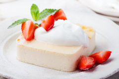 Pudding, cheesecake, custard dessert, with sour cream and fresh strawberry and mint leaves Stock Image