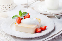 Pudding, cheesecake, custard dessert, with sour cream and fresh strawberry and mint leaves. On a white plate Stock Photography