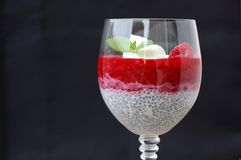 Pudding from chia seeds and raspberries with cottage with mint in glass on black background Royalty Free Stock Photo
