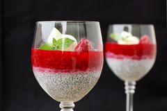 Pudding from chia seeds and raspberries with cottage with mint in glass on brown wooden background Stock Photo