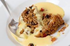 Pudding et crème anglaise d'université avec une cuillère Images stock