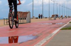 Puddle on the red bicycle line. Biker crossing puddle on the red bicycle line Royalty Free Stock Photos