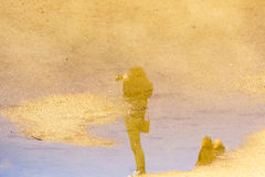 Puddle reflection of female photographer Stock Photography