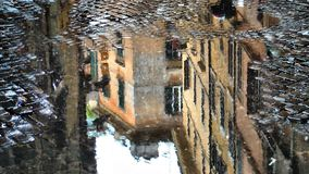 Puddle Reflection in the Rain Yellow Buildings 4K Loop. Features a view of a water puddle on a cobble stone street from above with the reflection of old stock video footage
