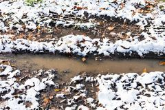 Puddle in track of dirty road covered with snow royalty free stock image
