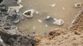 Puddle of water and mud in dirt soil an yellow sand stock video footage
