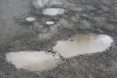 Puddles and potholes. On the road Royalty Free Stock Image