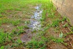Puddles after rain near the wall of a wooden house Royalty Free Stock Images