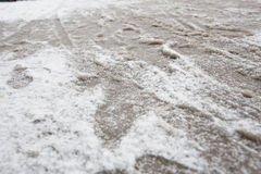 Puddles and slushy snow with footprints. Stock Image