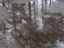 Puddles on the tile path. drizzle light rain.  stock photography