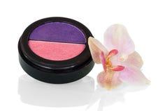 Pudełko dwa koloru dekoracyjnego suchego kosmetyka blisko Storczykowego kwiatu, odizolowywającego na bielu obraz royalty free