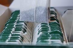 Pudełko herbaciane torby z zieleni etykietkami na wierzchołku Fotografia Stock