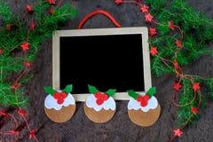 Pudim da decoração do Natal do cartão do feltro com estrelas vermelhas e o quadro preto Imagens de Stock Royalty Free