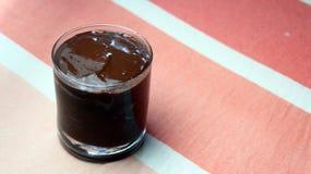 Pudim de chocolate em um copo de vidro no fundo cor-de-rosa Foto de Stock
