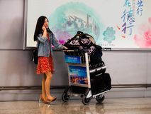 PUDONG, SHANGHAI, CHINA – 13 MAR 2019 – A solo Chinese female traveller with a full trolley of luggage at Pudong Airport royalty free stock image