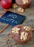 Pudrar fria muffin för gluten från bovete, äpplet, cinemon och valnötter på brun träbakgrund med indexkortet med text ingen glute Royaltyfri Fotografi