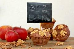 Pudrar fria muffin för gluten från bovete, äpplet, cinnamonandvalnötter på brun träbakgrund med indexkortet med text ingen glute Arkivfoto