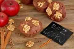 Pudrar fria muffin för gluten från bovete, äpplet, cinnamonandvalnötter på brun träbakgrund med indexkortet med text ingen glute Royaltyfri Bild