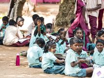 Group of children friends girls boys classmates studying with book sitting on floor outdoor at the school playground stock photo