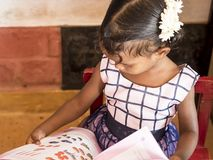 Cute beautiful kid reading in creche. PUDUCHERY, INDIA - DECEMBER Circa, 2018. Unidentified cute beautiful poor concentrated kid reading a book in the creche royalty free stock images