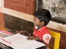 Cute beautiful kid reading in creche. PUDUCHERY, INDIA - DECEMBER Circa, 2018. Unidentified cute beautiful poor concentrated kid reading a book in the creche stock photography