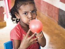 Cute beautiful kid inflatting a balloon in creche. PUDUCHERY, INDIA - DECEMBER Circa, 2018. Unidentified cute beautiful poor smiling kidindlatting balloon in the royalty free stock photos