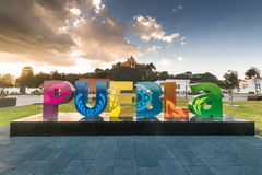 Puebla, Mexico. Puebla word made from big colorful letters in front of Cholula pyramid and Church of Our Lady of Remedies at the top Stock Images