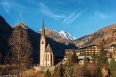 Pueblo alpino con la iglesia hermosa del peregrinaje y el cielo azul imagenes de archivo