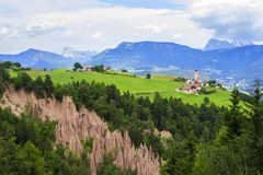 Pueblo alpino del paisaje de la opinión del fondo en una meseta rodeada por las montañas Rennon en el Tirol Fotos de archivo libres de regalías