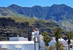 Pueblo blanco debajo de los altos picos, islas Canarias Fotografía de archivo libre de regalías