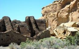 Pueblo Bonito Ruins at Chaco Canyon, Arizona. Ruins of the ancient town of Pueblo Bonito stand next to a wall of natural stone at Chaco Canyon Stock Photos